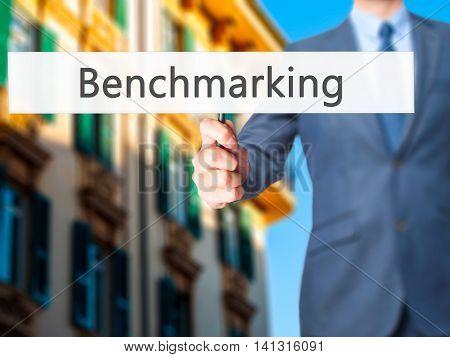 Benchmarking - Businessman Hand Holding Sign