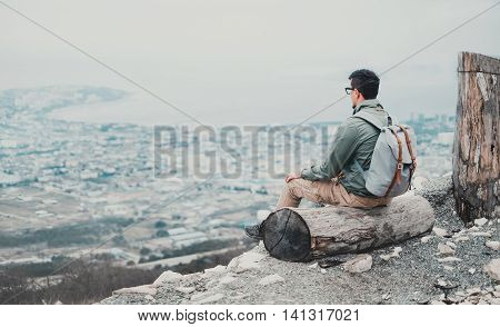 Traveler young man sitting on tree trunk and looking at town