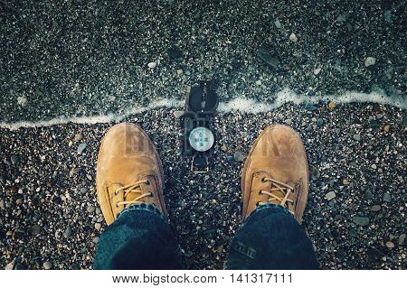 Compass on pebble shore near legs of traveler man outdoor. Point of view shot.