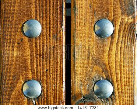 A fragment of a wooden bench. Brown polished boards, bolted.
