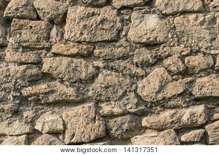 Old wall of large irregular pieces of stone ruins brown background detail