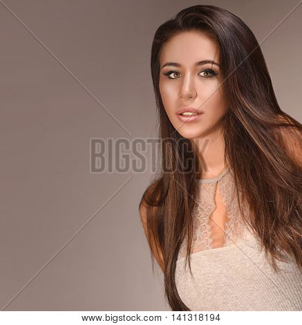 beauty portrait of attractive young caucasian woman brunette studio shot face long hair head and shoulders looking at camera lips eyes