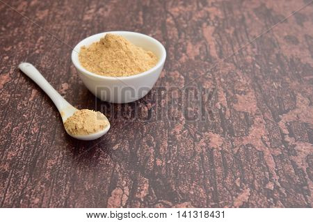 Maca powder on rustic background. Super food