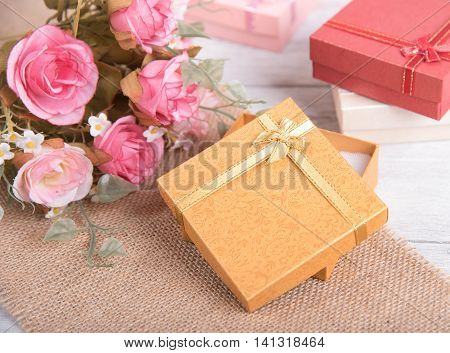 Vintage gift box and pink rose flower on wooden background