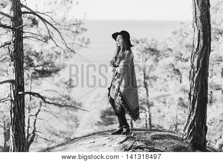 Beautiful young woman in poncho and hat standing among pine trees in the forest. Monochrome image