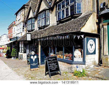 BURFORD, UNITED KINGDOM - JULY 20, 2016 - Shops along The Hill shopping street with the cheese shop in the foreground Burford Oxfordshire England UK Western Europe, July 20, 2016.