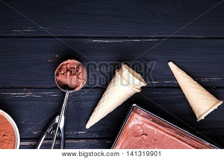 Chocolate ice cream and waffle cones on black background top view