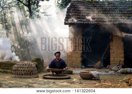 HANOI, VIETNAM, JULY 24, 2016: Countryside old woman do farmer work in a village in suburb of Hanoi, Vietnam.