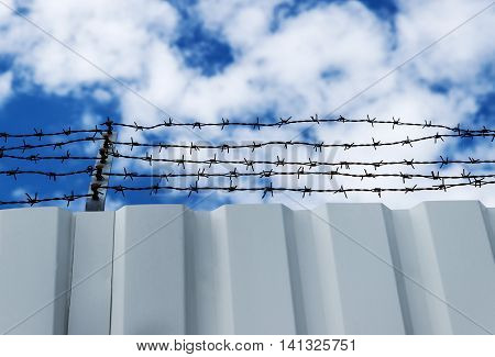 Rusty barbed wire against the beautiful blue sky
