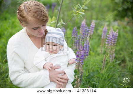 Young mother with baby at meadow lupins flowers. Soft focus on baby
