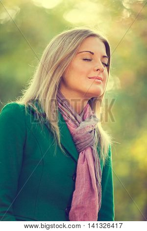 Young woman is enjoying fresh air in autumn, intentionally toned.