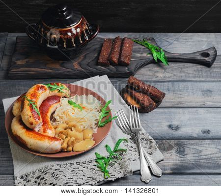 Sauerkraut with fried Munich sausages pickled mushrooms fresh green lettuce silver forks ceramic kstrblya rye bread croutons on linen lace napkin gray wooden background in rustic style