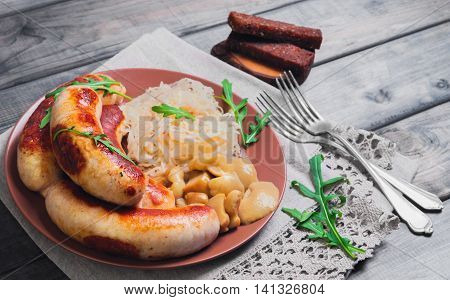 Sauerkraut with fried Munich sausages pickled mushrooms fresh green lettuce silver forks rye bread croutons on linen lace napkin gray wooden background in rustic style