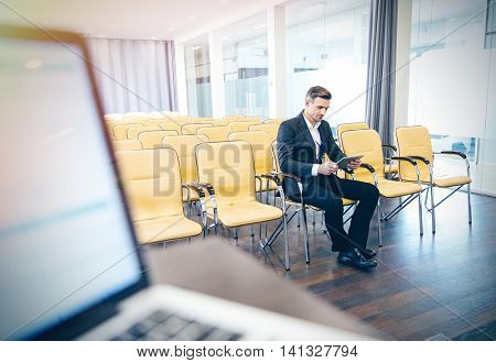 Pensive focused businessman sitting and using tablet in empty conference hall