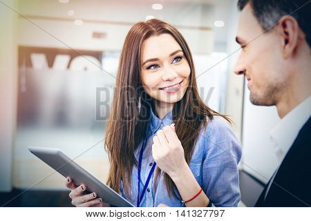 Happy pretty young business woman talking to her client and using tablet