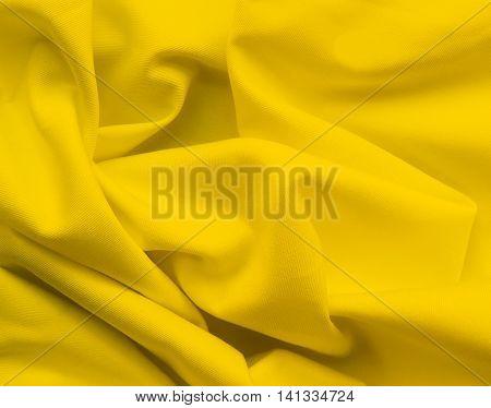Yellow cloth or textile, wavy textile, close-up shot.