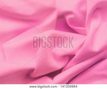 Pink cloth or textile, wavy textile, close-up shot.