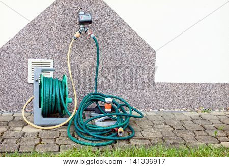 Garden irrigation equipment against house wall and ready to use