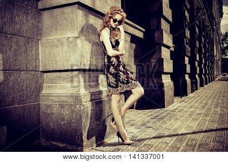 Beautiful fashionable woman standing on the city street. Fashion shot. Sepia.