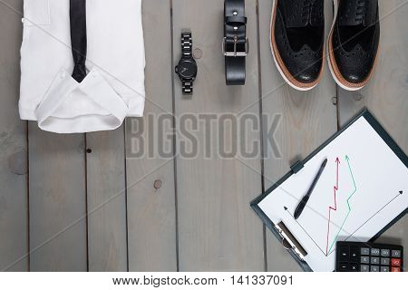 Businessman work outfit on grey wooden background. White shirt with black tie watch belt oxford shoes planchette and calculator. Back to work. Copy space frame. Set of mans fashion and accessories.