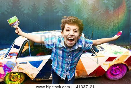 teenage handsome boy with brush and graffiti spray on the old painted retro car background closeup portrait on the blue wall background