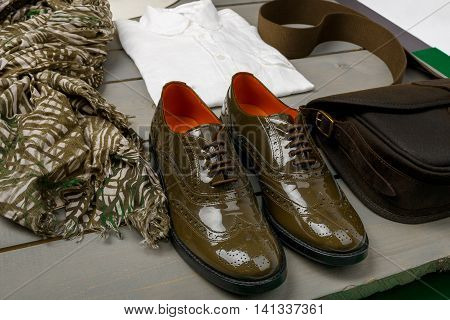 Green lacquered oxford shoes near white shirt bag and scarf on wooden background. Back view.