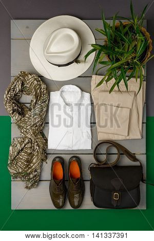 Women's outfit on wooden background. fashion clothes. beige straw hat beige pant white shirt green scarf black crossbody bag and oxford shoes near flower pot. Top view.
