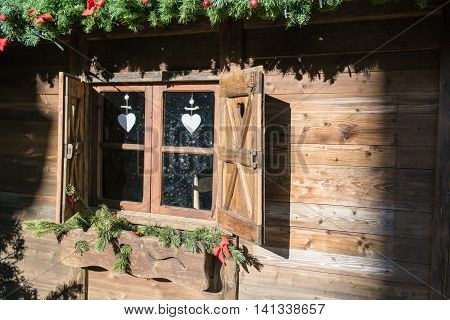 Wooden window of an alpine hut decked out for Christmas.