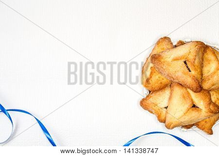 Hamantaschen or Haman's ears - triangular cookies for Jewish holiday of Purim, on light background