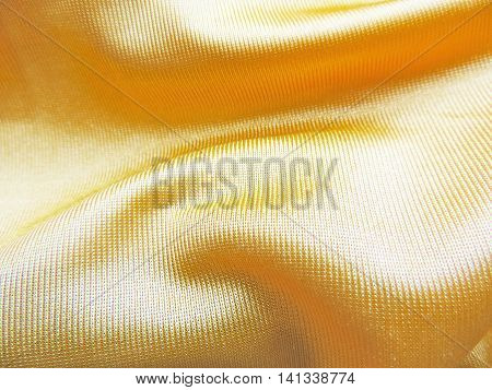 Golden satin textile or cloth, closeup. Textile background.