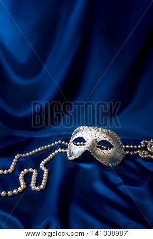 Silver carnival mask and pearl on dark blue silk background
