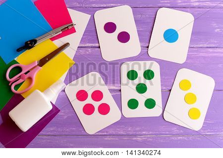 Colored flash cards for toddler, preschooler. How to teach colors to kid. How to teach child to count. Flashcards, scissors, cardboard on wooden background. Early development in kindergarten, at home