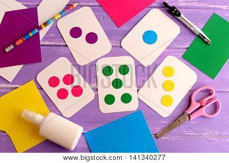 Colored flash cards for toddler, preschooler, kindergarten. How to teach kid to read colors. How to teach a child to count. Flashcards, scissors, pencil, cardboard on wooden background. Early learning