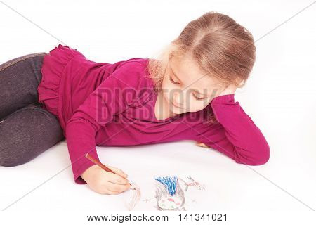 Little cute girl draws pencils lying on the floor on a white background