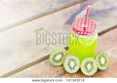 Kiwi juice and kiwi slices on a wooden table