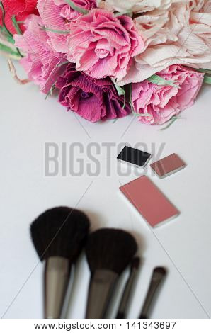 Makeup brushes cosmetics eyeshadow, blush brushes, mirror, eye shadow, paper flowers on a white background
