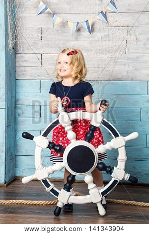 Little girl hold steering wheel and looking away