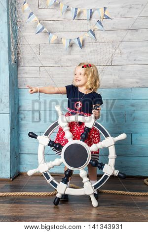 Little girl holding steering wheel and shows his hand towards