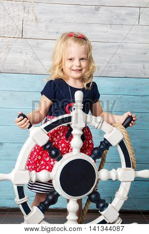 Little girl hold steering wheel and looking at camera