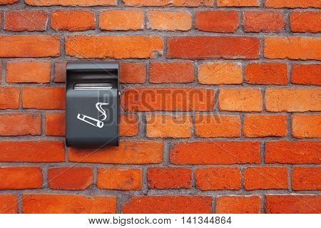 Special place for smoking.Grey ashtray on an old brick wall.