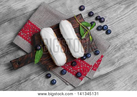 Two French Cake eclairs with white icing on wooden board burlap cloth with red lace mint leaves Blueberry berries for filling eclairs