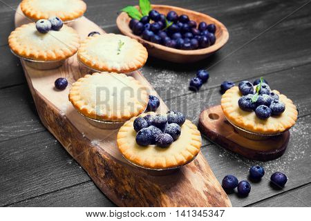 Closed berry tartlets baskets Cake with berries blueberries into molds foil for tartlets on olive wooden board mint leaves blueberry berries in bowl on black surface