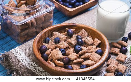 Multigrain healthy cereal corn pads chocolate in white bowl for milk breakfast glass of milk cereal bank cereal is scattered on table blueberries bilberries blue wooden background