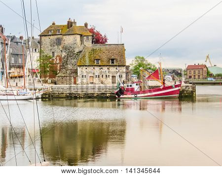 Old boat and The Lieutenancy building or La Lieutenance is at the entrance to the old harbour. Honfleur, Normandy, France
