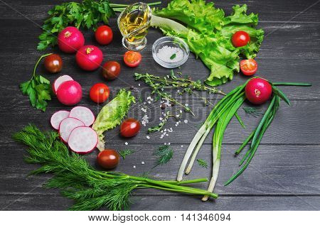 Ingredients for the preparation of fresh vegetarian vegetable salad vegetables radishes cherry tomatoes lettuce green salad dill parsley allspice salt olive oil and thyme on a dark black wooden background
