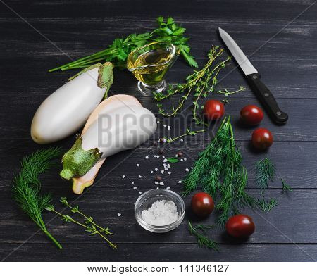 Cooking vegetable vegetarian ragout salad of white eggplant cherry tomatoes thyme dill sweet pepper vegetable oil salt black knife on dark wooden background surface