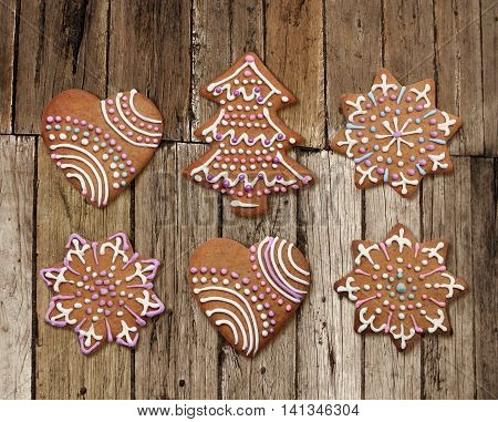 Decorated Christmas gingerbreads on old rough wood plank background