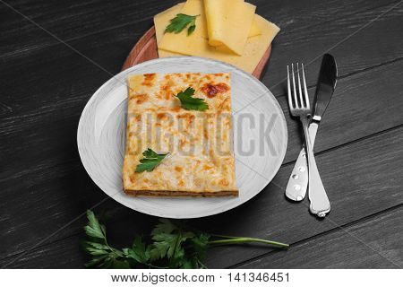 Homemade meat lasagna with Bolognese sauce pieces of cheese for lasagna green parsley on plate dark black wooden background