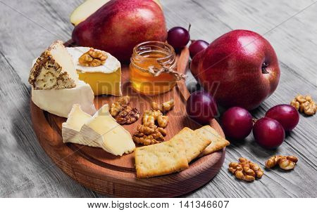 Fruit pear whole grapes pear cut in half cheese. Camembert cheese goat cheese honey walnuts on light white wooden background