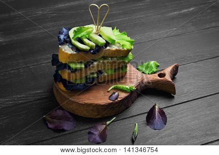 High large layered sandwich with avocado lettuce cheese ricotta on acutting board on dark black wooden background